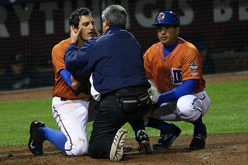 Bulls infielder Mikie Mahtook is examined by trainer Mike Sandoval after being hit in the head by a pitch. Bulls manager Charlie Montoyo is at right.