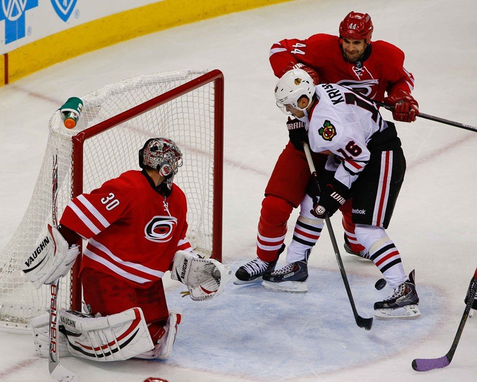 Cam Ward watches defenseman Jay Harrison clear Marcus Kruger from his goal crease. Chicago beat the Canes in a shootout, 3-2.
