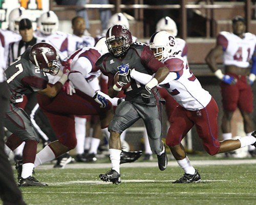 Adrian Wilkins carries the ball while Tevin Richard (32) makes the tackle for the Bulldogs.