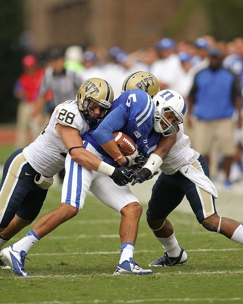 Brandon Braxton is wrapped up by Anthony Gonzalez (28) and a Pitt teammate.