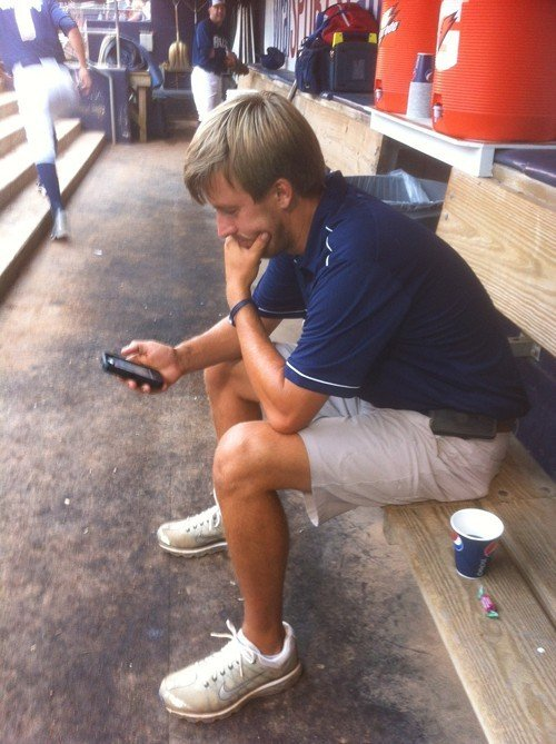 Bulls groundskeeper Scott Strickland, watching radar on his phone.