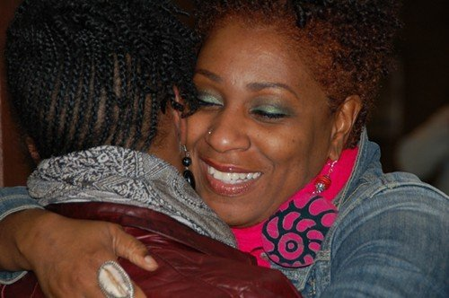 Omisade Burney-Scott, a laid-off YWCA staffer, embraces Letha Muhammad.