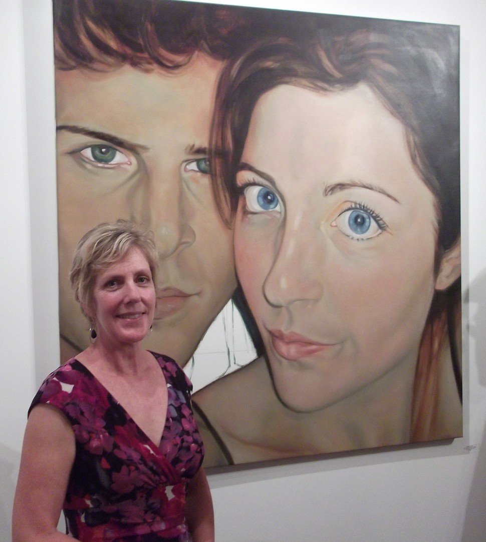 Charlton poses with one of her new works at her Eno Gallery opening in Hillsborough