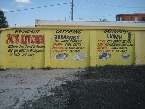 Hand lettering on the side of J.C.s Kitchen advertises the restaurant's specials.
