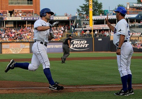 Russ Canzler high-fives Durham Bulls manager Charlie Montoyo as he rounds third base.
