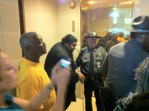 The Rev. William Barber being led away in handcuffs