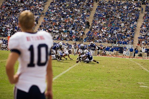 A University of Virginia player watches as a Duke player recovers a fumble in a 2008 game. Duke opens its 2010 campaign tomorrow, hosting Elon University at Wallace Wade Stadium.
